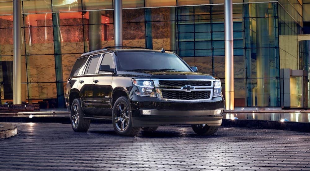 A black 2017 Chevy Tahoe is parked in front of a glass building after leaving a GA used car dealer.
