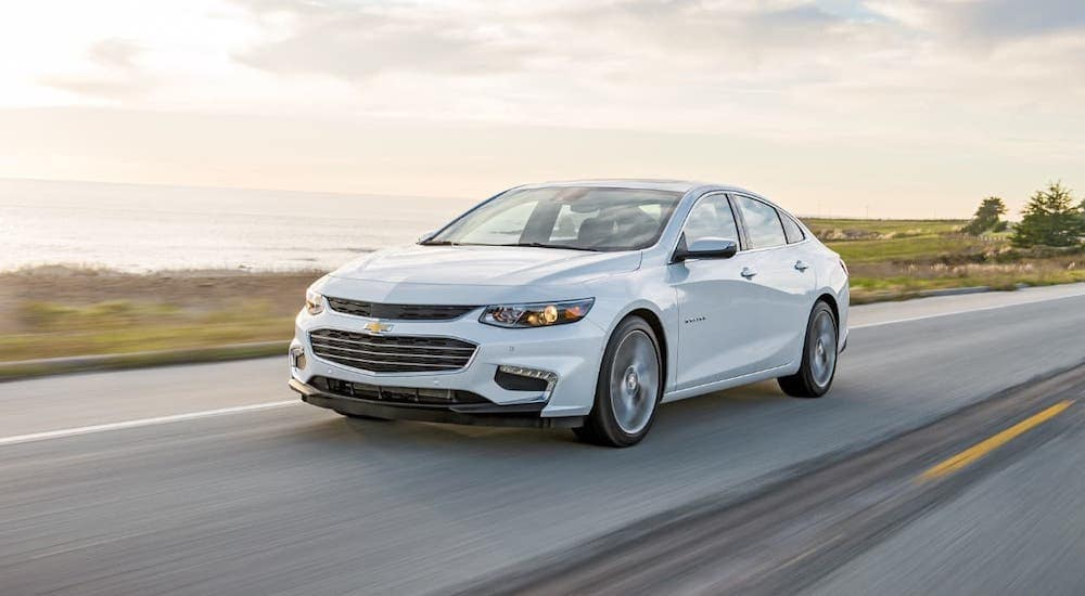 A white 2018 Chevy Malibu is driving along a coastal highway.