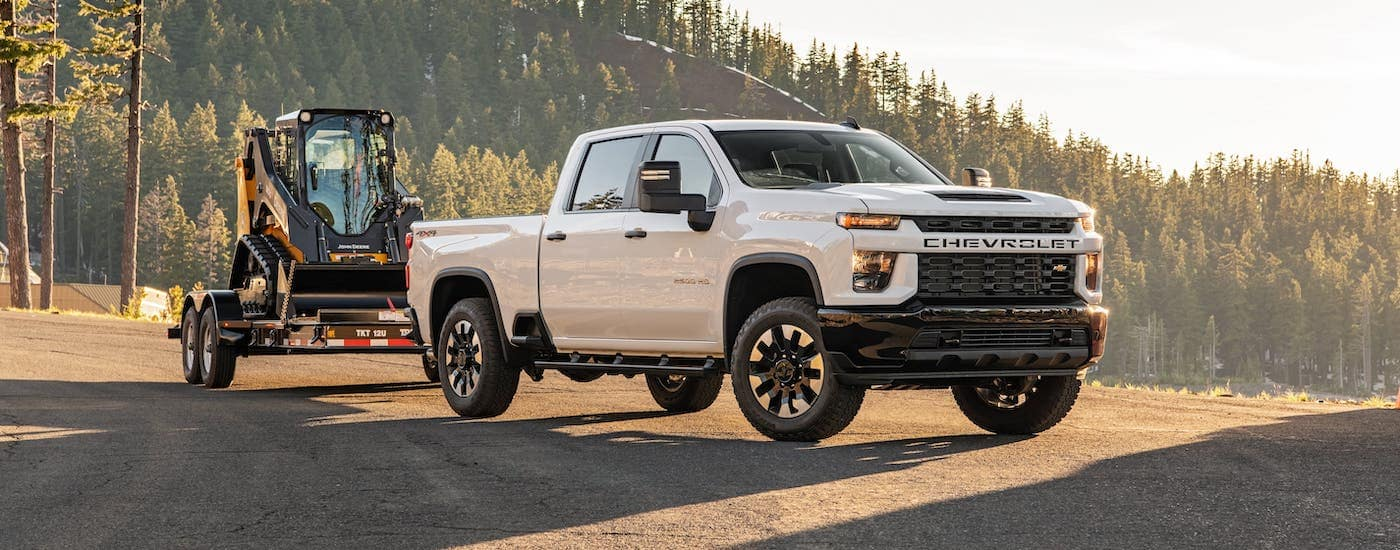 A white 2020 Chevy Silverado 2500HD is towing construction equipment on a mountain road.