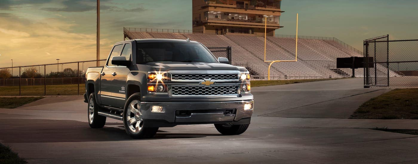 A popular used Chevy truck, a black 2016 Chevy Silverado 1500, is parked in front of a football field.