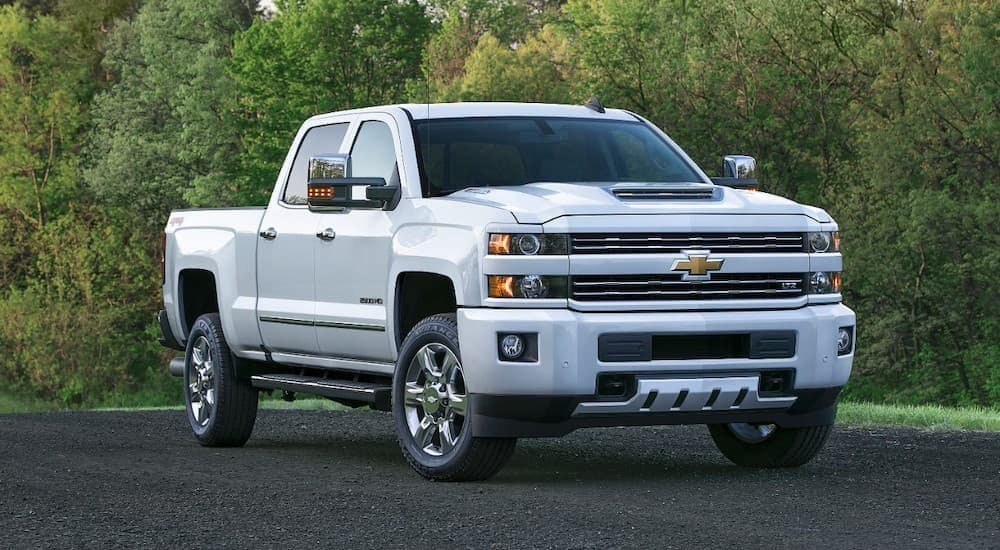 A popular used Chevy truck, a white 2017 Chevy Silverado 2500HD is parked in front of trees.