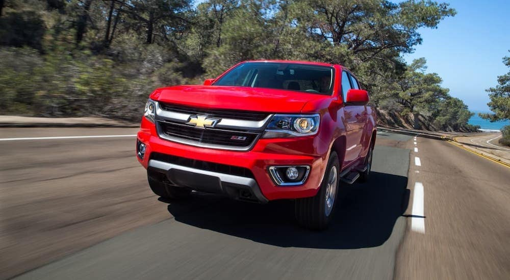 A red 2017 Chevy Colorado Z71 is driving on a road and shown from the front.