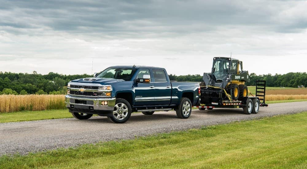 A blue 2018 Chevy Silverado 2500HD is towing construction equipment on a dirt road past fields.