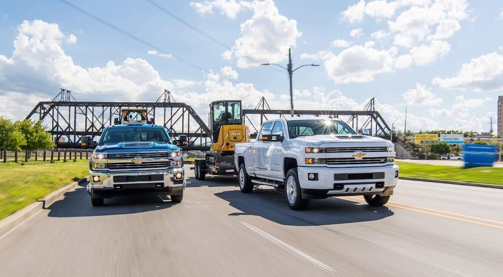 A white and a blue 2018 Chevy Silverado 2500HD are towing construction equipment past a bridge on a highway.