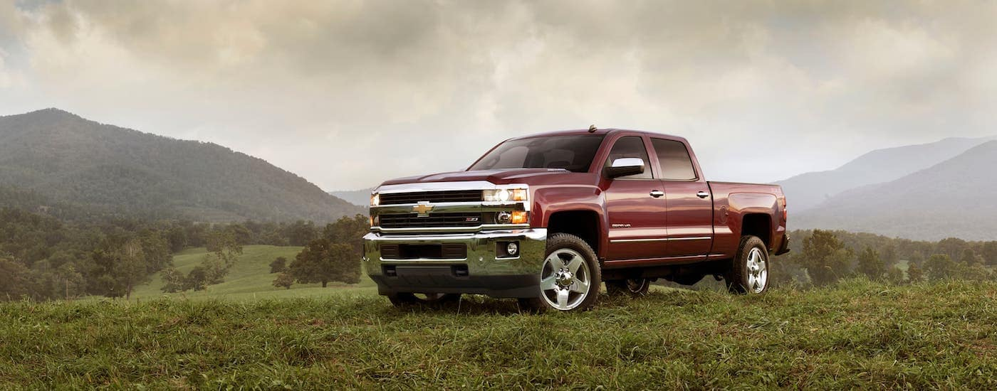 A dark red 2018 Chevy Silverado 2500HD is parked on a field.