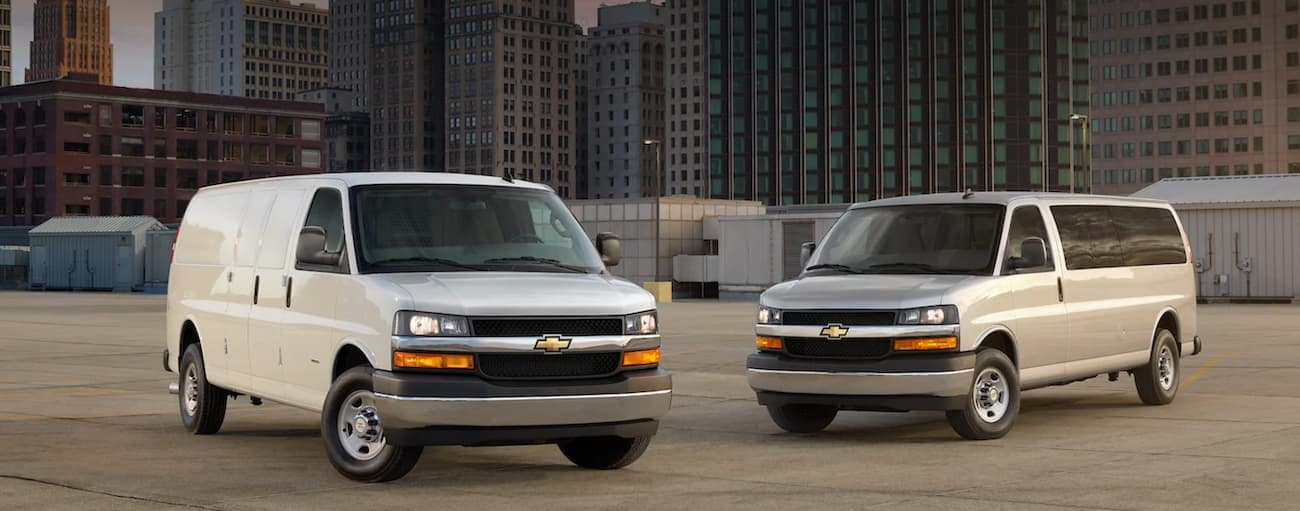 A white and a silver 2021 Chevy Express are parked in an empty lot in front of city buildings.