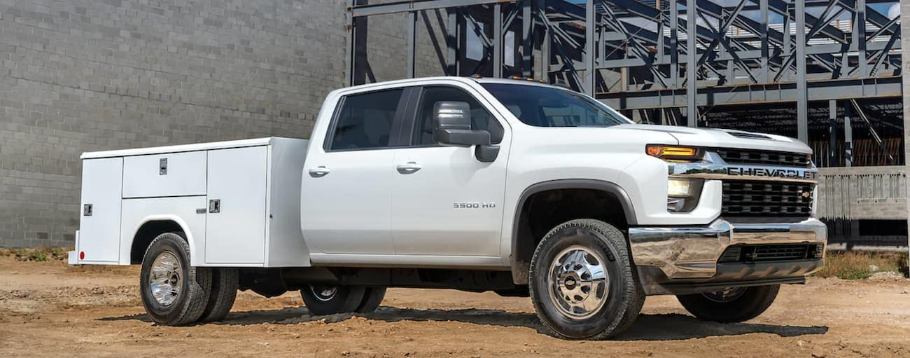 A white 2021 Chevy Silverado 3500 HD Chassis Cab with a utility bed is at a construction site.