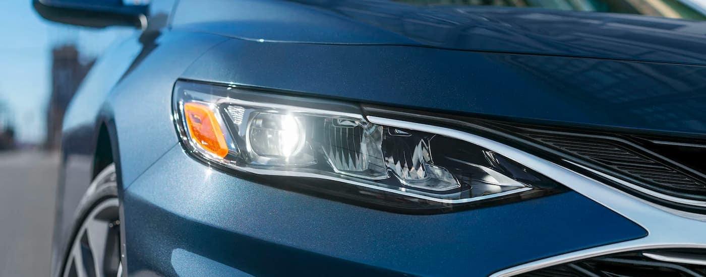A close up shows the chrome headlight on a blue 2021 Chevy Malibu.