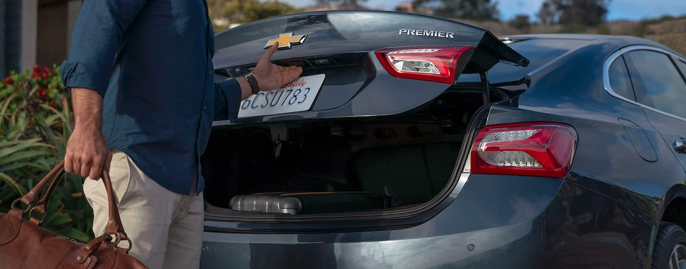 A man is shown putting luggage in the trunk of a dark gray 2021 Chevy Malibu.
