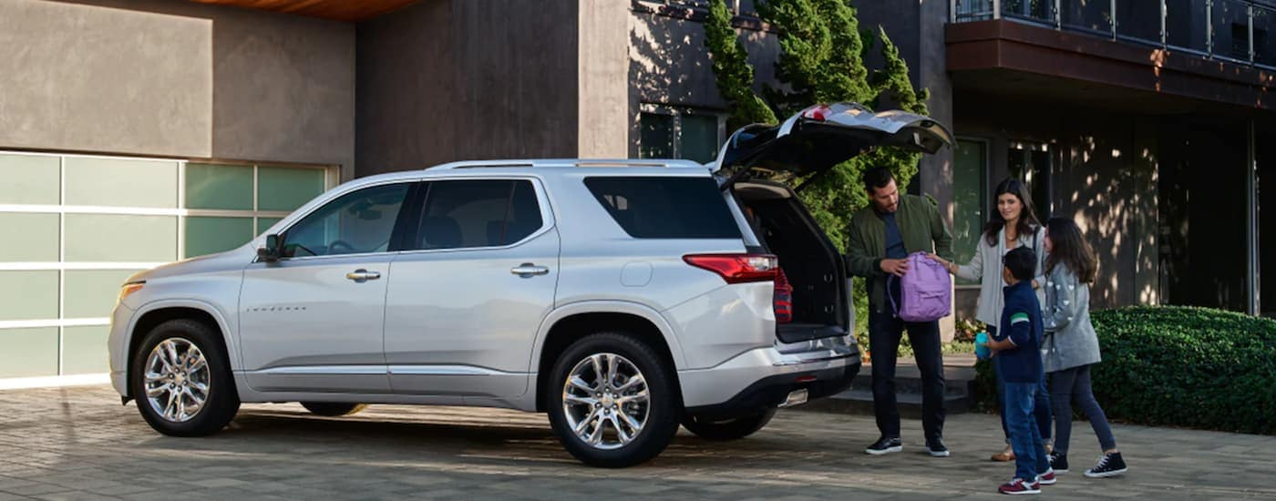 A silver 2021 Chevy Traverse is shown from the side with a father putting a back pack in the trunk.