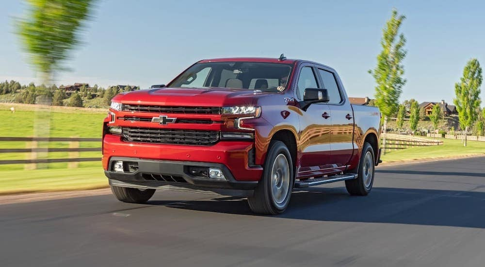 A red 2020 Chevy Silverado 1500 is driving on an empty road.