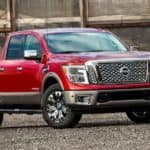 A red 2018 Nissan Titan from an Atlanta Used Truck Dealer is parked in front of a brick building.