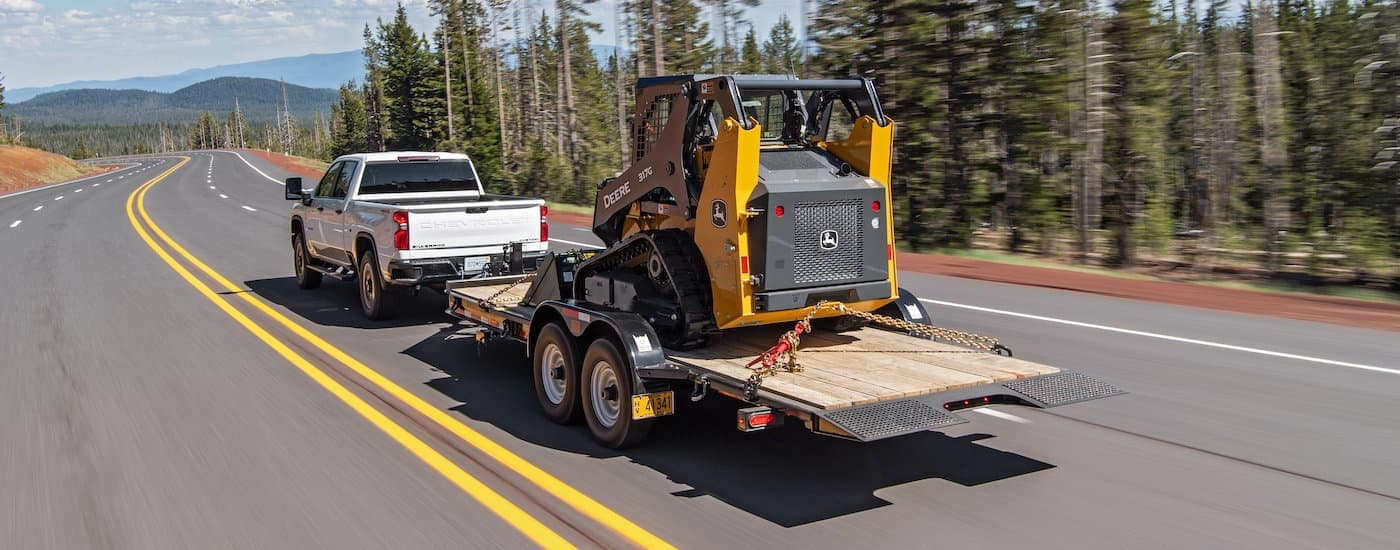 A white 2021 Chevy Silverado 2500 HD is shown from behind towing construction equipment down a tree-lined highway.