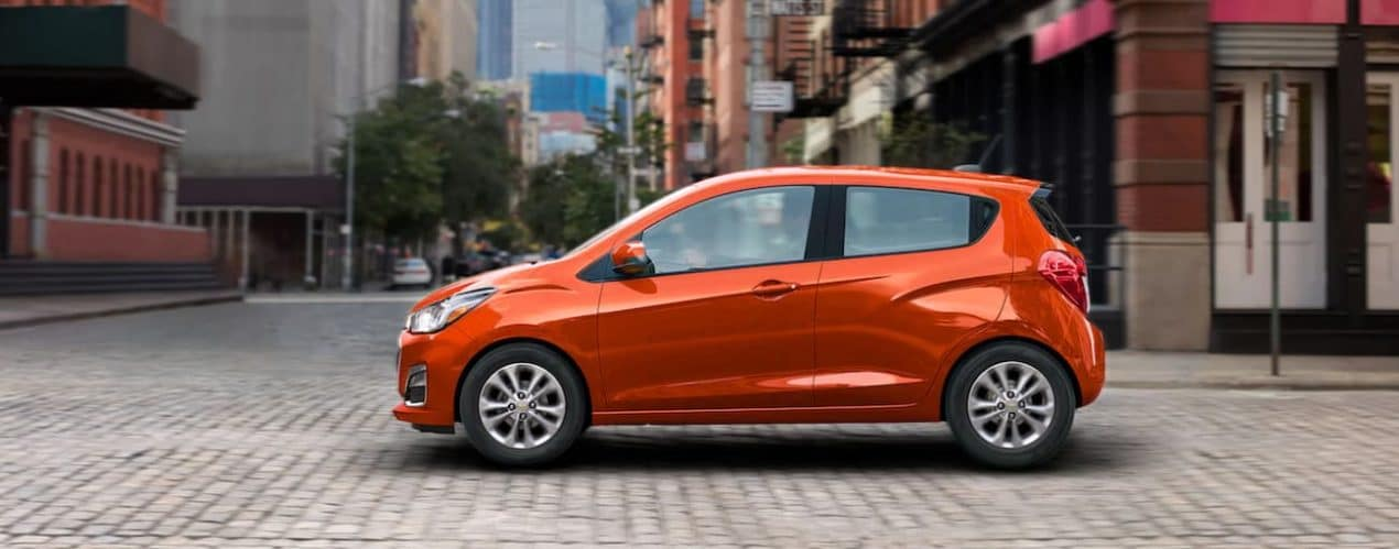 An orange 2021 Chevy Spark is shown from the side driving on a brick street in a city after winning the 2021 Chevy Spark vs 2021 Mitsubishi Mirage comparison.