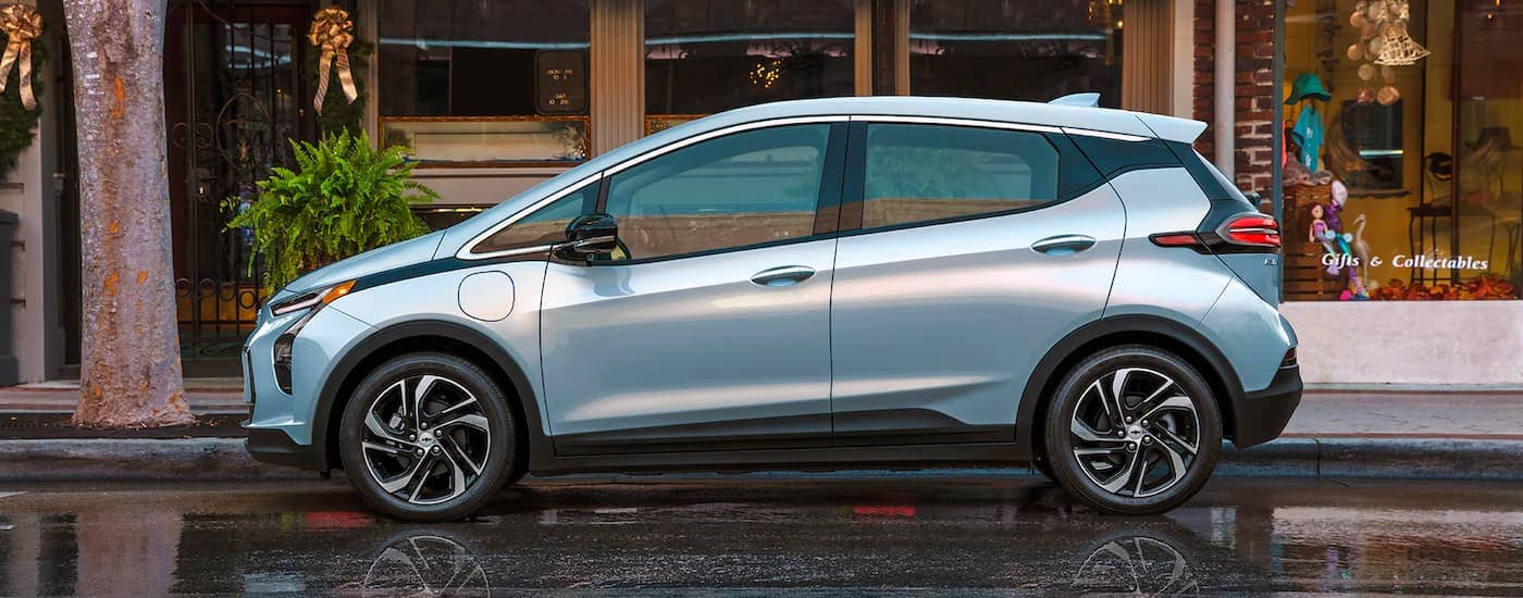 A pale blue 2022 Chevy Bolt EV is shown from the side parked in front of a shop.