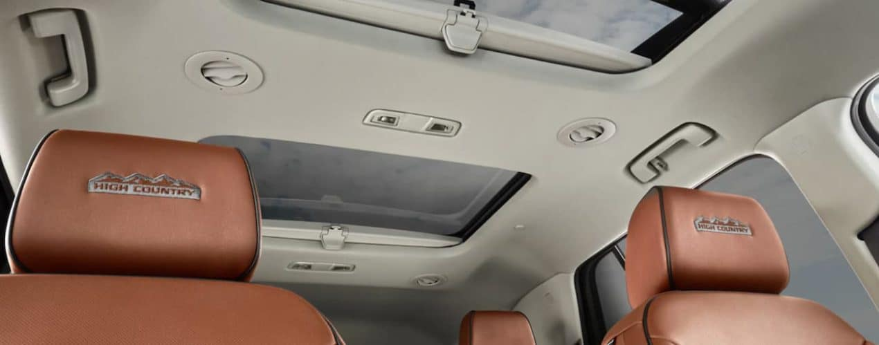 The brown seats and sunroof in a 2021 Chevy Traverse High Country is shown from the inside.