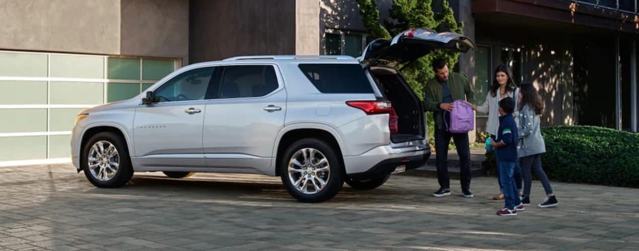 A family is putting luggage in the open trunk of a silver 2021 Chevy Traverse after it won the 2021 Chevy Traverse vs 2021 Dodge Durango comparison.