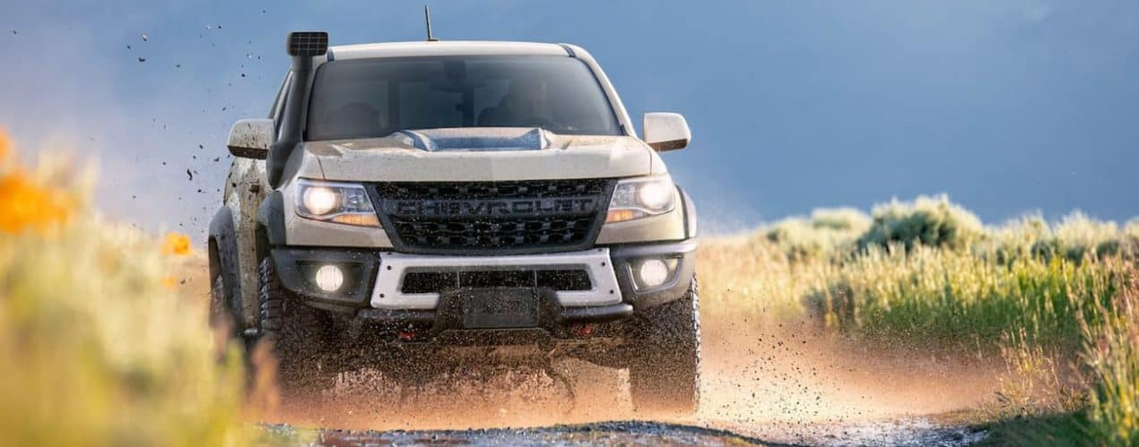 A tan 2021 Chevy Colorado ZR2 is off-roading on a muddy path.