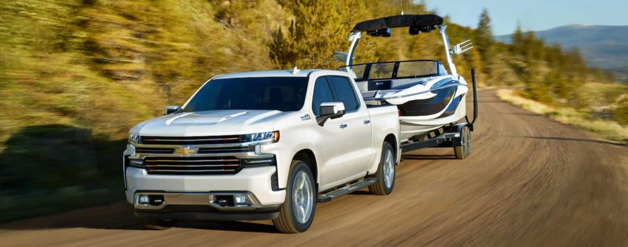 A white 2021 Chevy Silverado 1500 is towing a boat around a corner past bushes.
