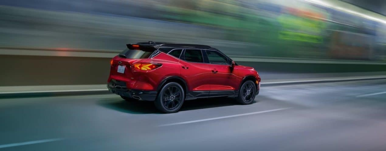 A red 2022 Chevy Blazer is driving down a highway.