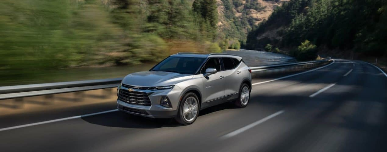 A silver 2022 Chevy Blazer is driving along a tree lined road.