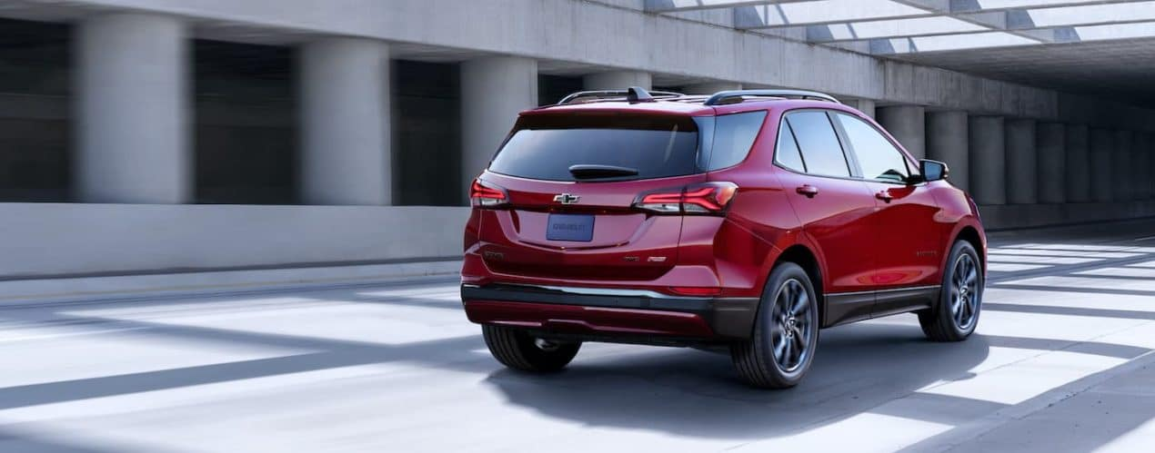 A red 2022 Chevy Equinox RS is shown driving past concrete columns.