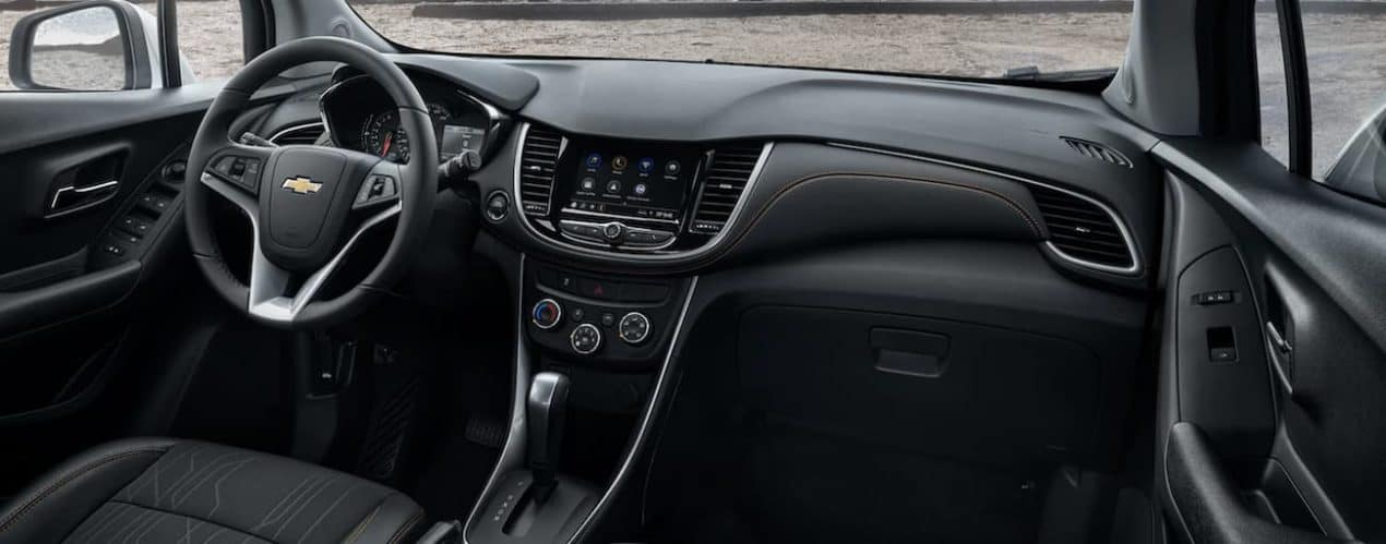 The interior of a 2022 Chevy Trax shows the steering wheel and infotainment screen.
