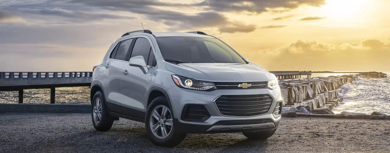 A silver 2022 Chevy Trax is parked on a jetty at sunset.