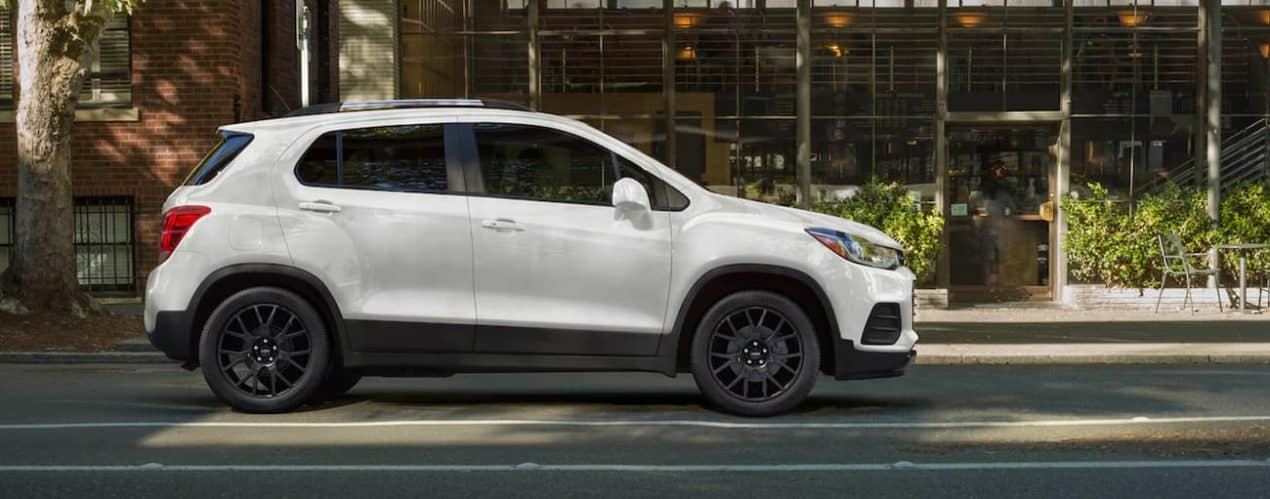 A white 2022 Chevy Trax is shown from the side driving on a city street.