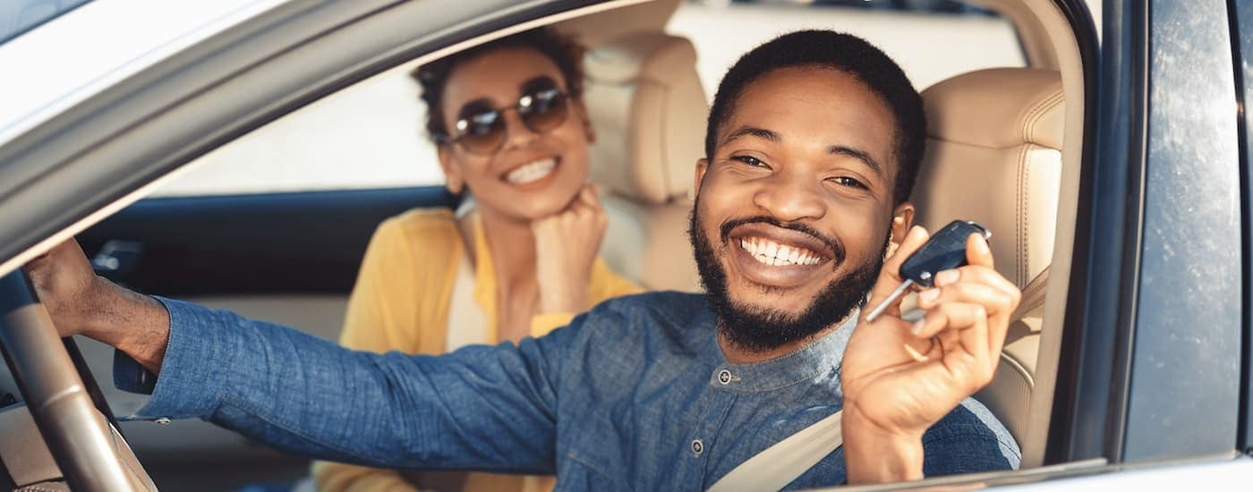 A couple is holding a set of car keys while sitting in the front seats of a used car.
