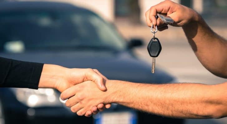 A salesman is shaking hands at an Atlanta used Chevy dealer.