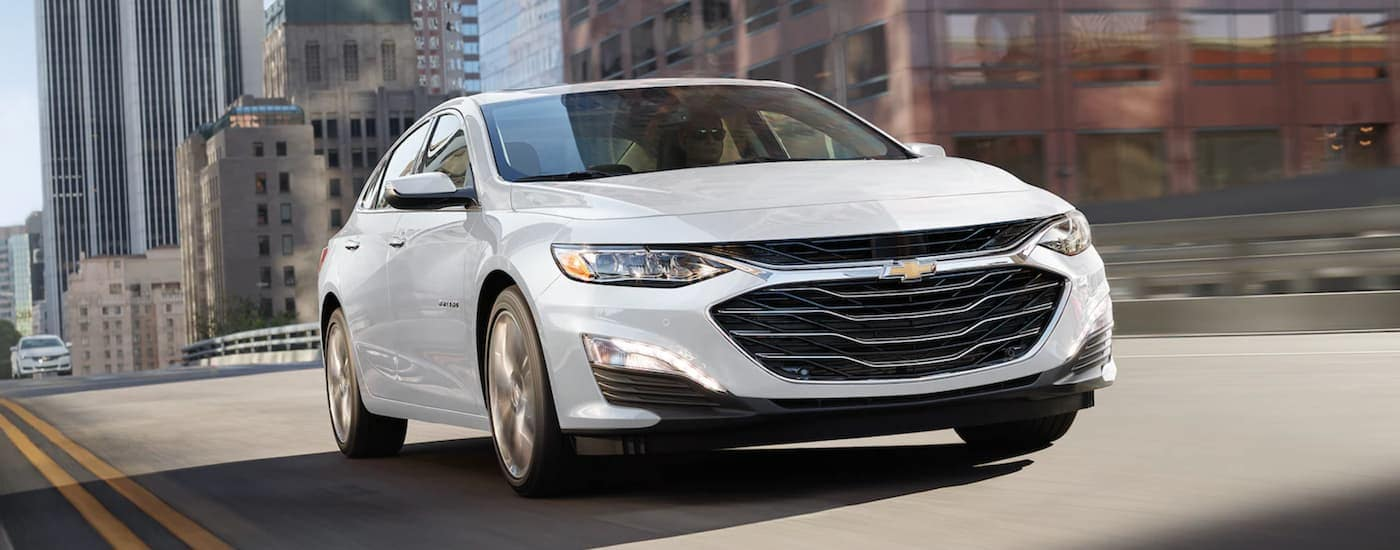 A white 2021 Chevy Malibu is shown from the front driving through a city.