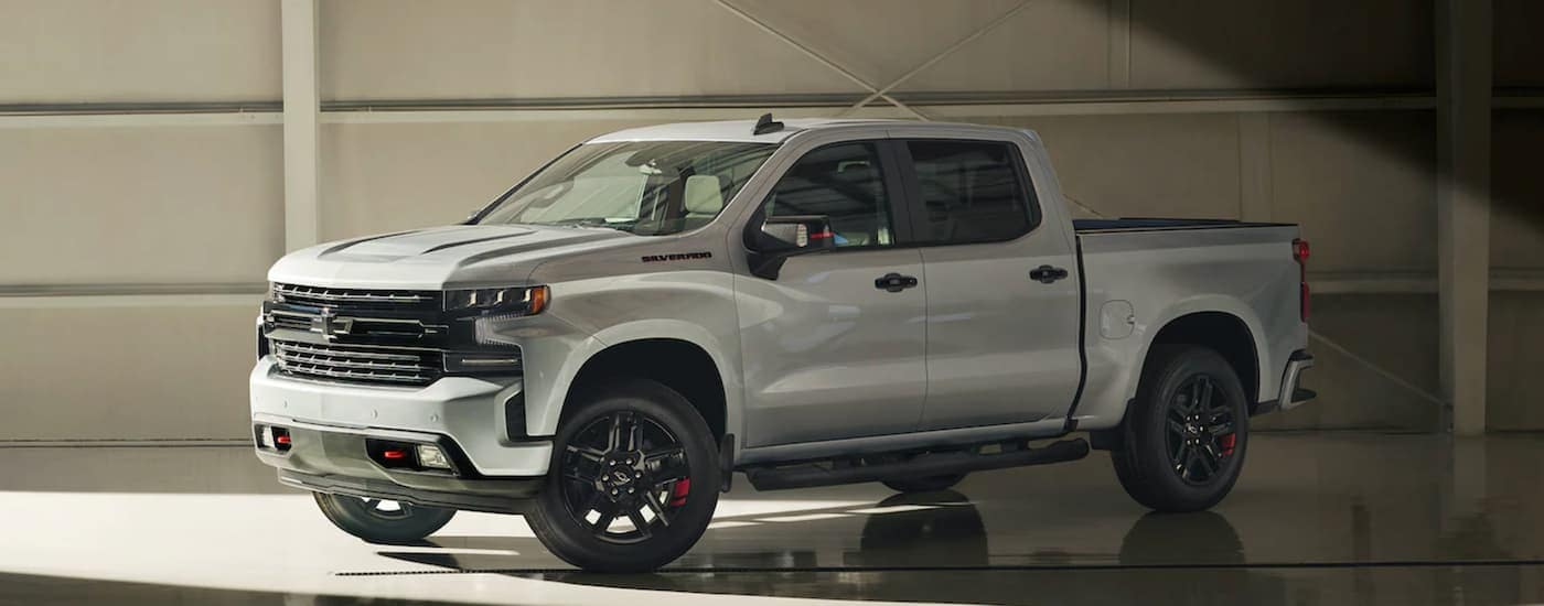 A silver 2021 Chevy Silverado 1500 is shown parked in a modern gallery.
