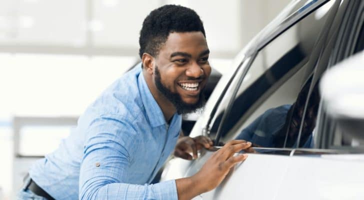 A man is smiling looking at new Chevy vehicles in stock.