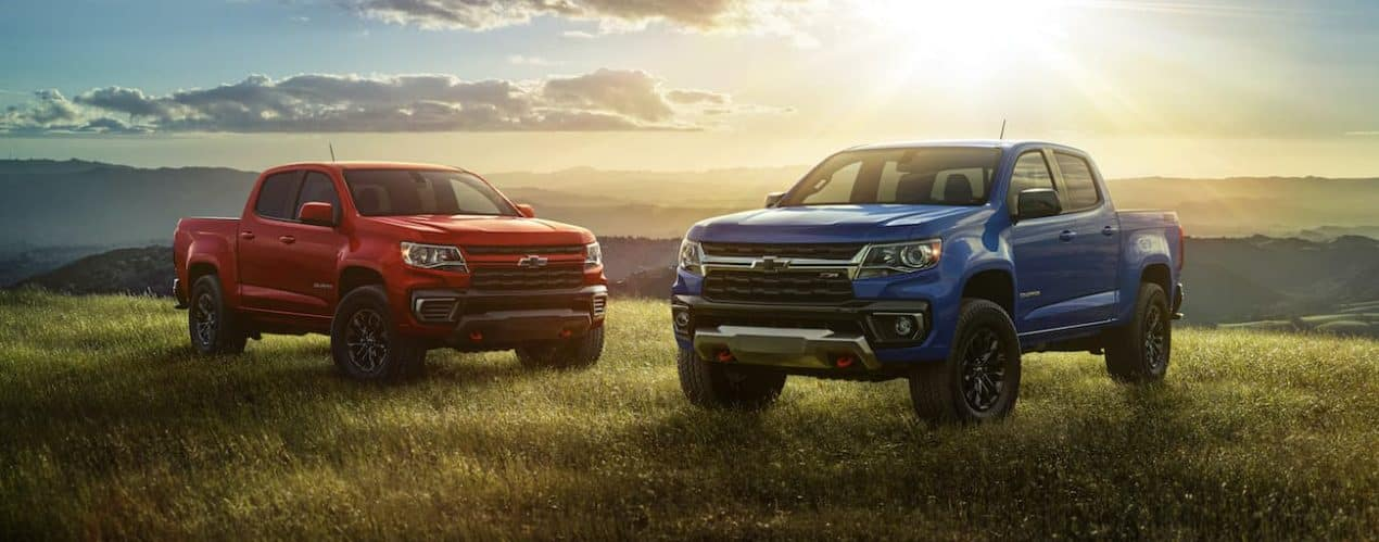 A red and a blue 2022 Chevy Colorado are shown parked in a field.