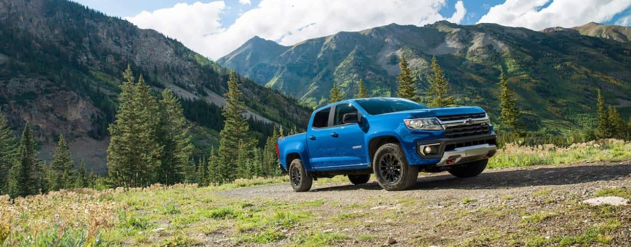 A blue 2022 chevy Colorado is shown off-roading in a field.