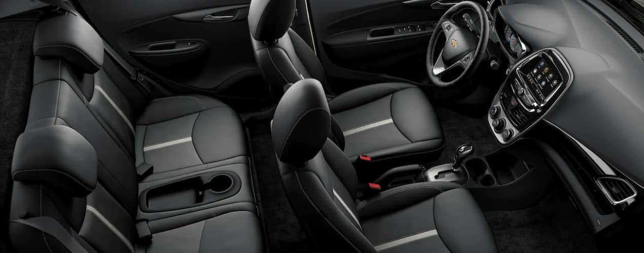 The black interior of a 2022 Chevy Spark shows 4 seats.
