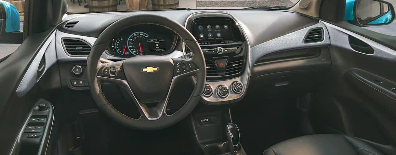 The black interior of a 2022 Chevy Spark shows the steering wheel and infotainment screen.