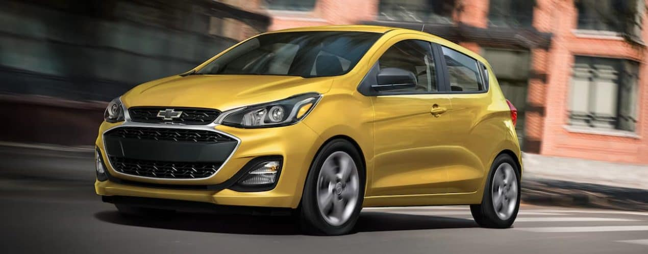 A yellow 2022 Chevy Spark is shown driving through a city.