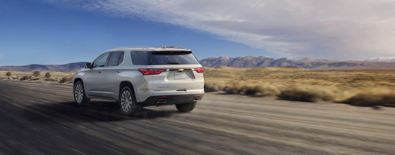 A silver 2022 Chevy Traverse is shown from the rear driving on an open road.