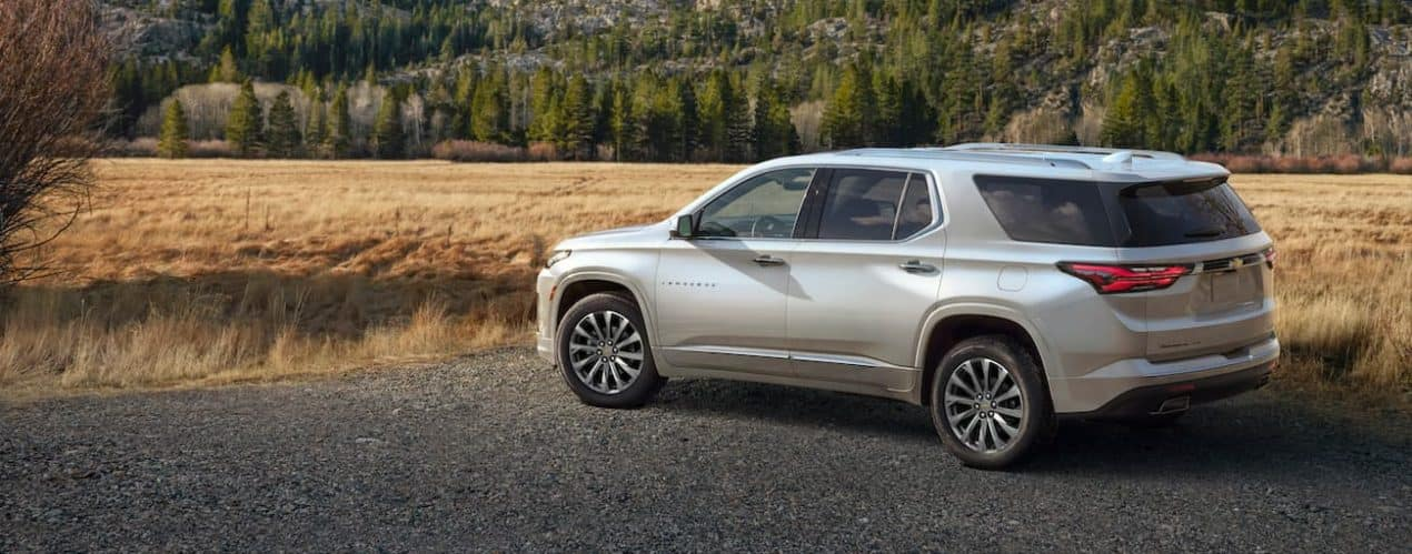 A silver 2022 Chevy Traverse is shown parked in front of a field.