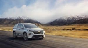 A silver 2022 Chevy Traverse is shown driving on an open road.