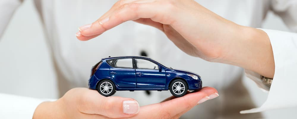 Hands protecting a toy car