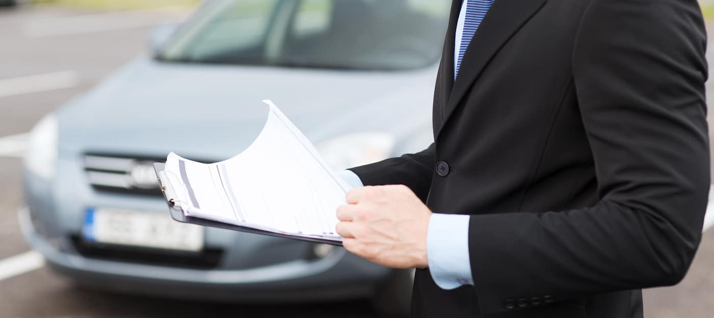man with car documents outside