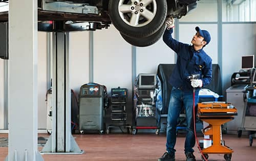 Mechanic checks the undercarriage of a vehicle that is lifted up in the air