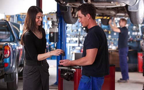 Woman hands her keys to a mechanic