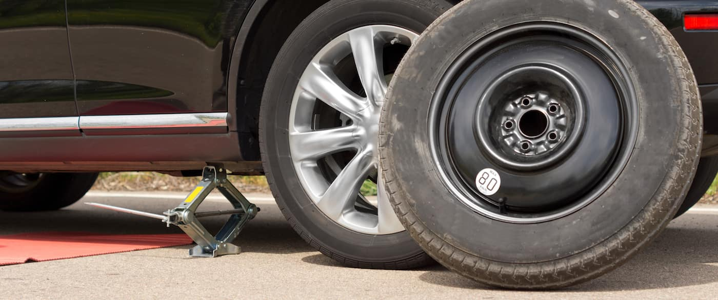 Changing the wheel on a car with the vehicle jacked up on a hydraulic jack and the spare wheel propped up against the front side of the car close up view
