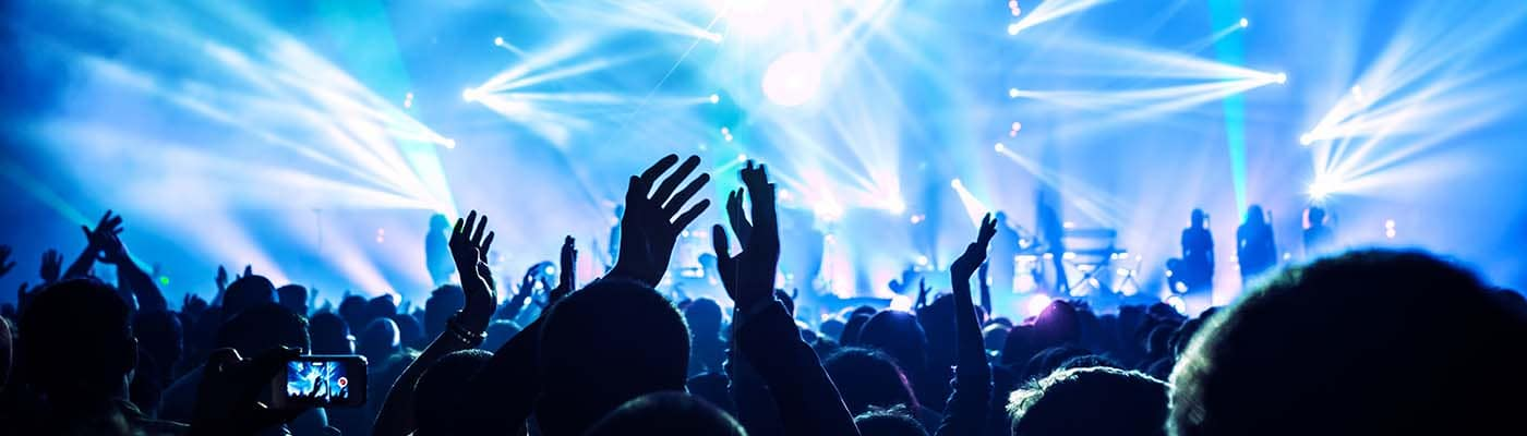 Large group of happy people enjoying rock concert, clapping with raised up hands, blue lights from the stage
