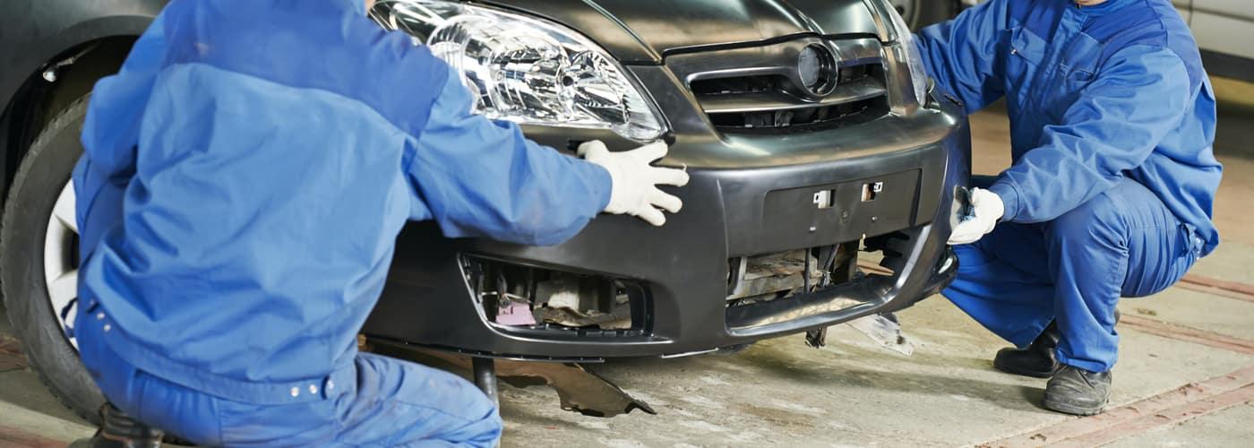 Two mechanics working on a car bumper