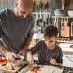Father with two kids preparing pizza at home